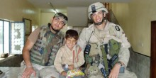 Photo of Michael Miranda and his interpreter with a neighborhood child while on mission in Iraq