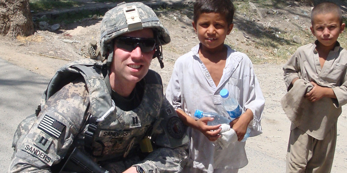 Photo of Capt. Chris Sanders ('08) in uniform with children