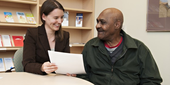 Photo of woman administering senior services to a man