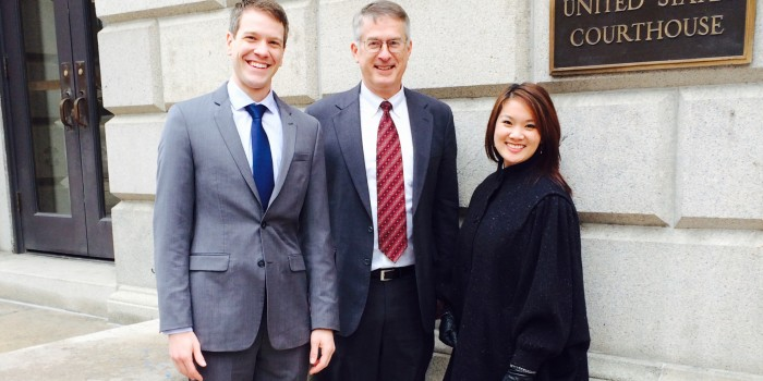 Group photo of Pat Wallace ('14), Professor John Korzen ('91) and Tammy Hsu ('14) pose outside the United States Court of Appeals for the Fourth Circuit, in Richmond, Va., on Jan. 28.