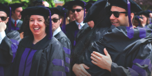 Photo of students hugging at hooding ceremony