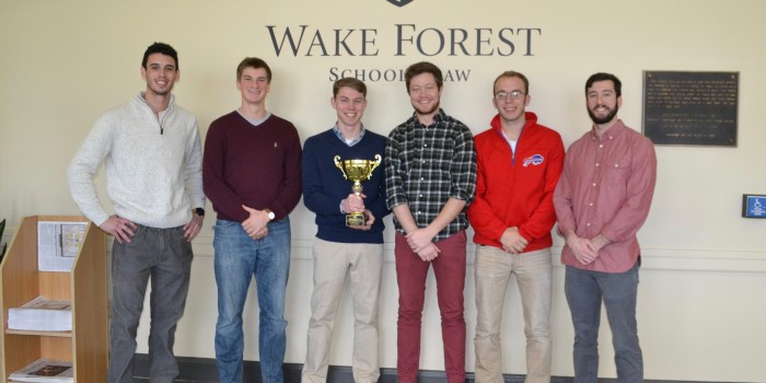 Group photo of trial competition students with trophy