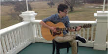 Photo of Braiden Sunshine playing the guitar on a porch