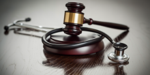 Photo of gavel and stethoscope on table
