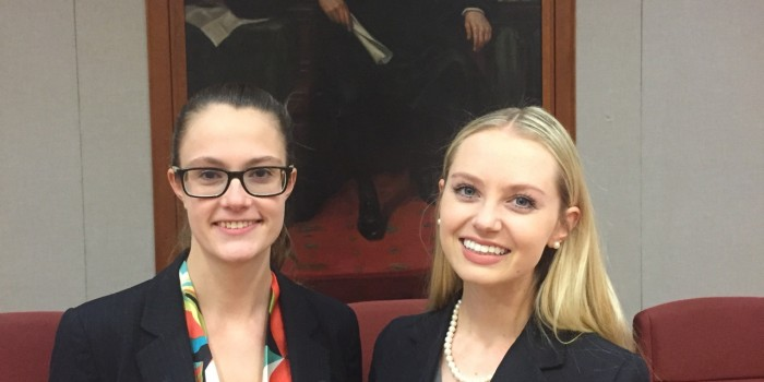 Photo of law students Ashley DiMunzio (JD '19) and Paige Tucker (JD '19) in large courtroom