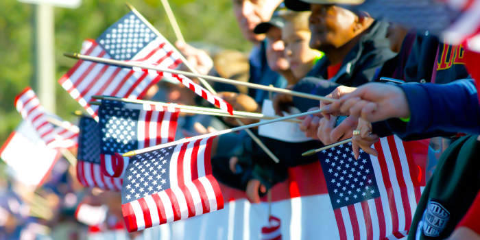 Photo of people holding small American flags at a parade