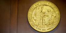 Photo of gold North Carolina seal on wall that says, 'The Great Seal of the State of North Carolina April 12 1776 Esse Quam Viberu'