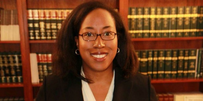 Photo of alumna, Latia Ward (JD '06), in front of a row of book cases in a library