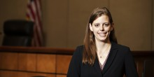 Photo of Kaitlin Price (BA '13, JD '16) standing in courtroom of the North Carolina Business Court in Greensboro
