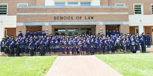 Photo of the Class of 2017 in their cap and gowns in front of the law school.