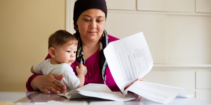 Photo of mother with baby looking through legal documents