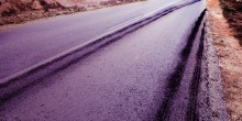 Stock photo image of asphalt on an empty highway. showing tire marks leaving the road.