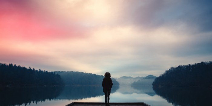 Stock photo of silhouette of the back of a woman standing on jetty on a lake staring at the pink sunrise over the mountains.