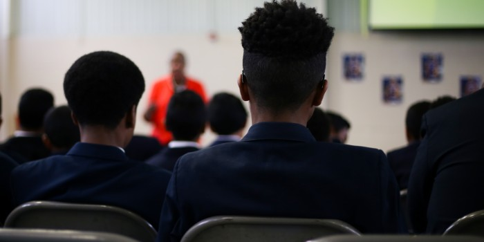 Photo of two middle school students watching Forsyth County Judge Denise Hartsfield (JD '91) speak during the Pro Bono Project's 'Know Your Rights' event
