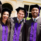 Photo of a group of happy law graduates standing in their robes outside Wait Chapel.