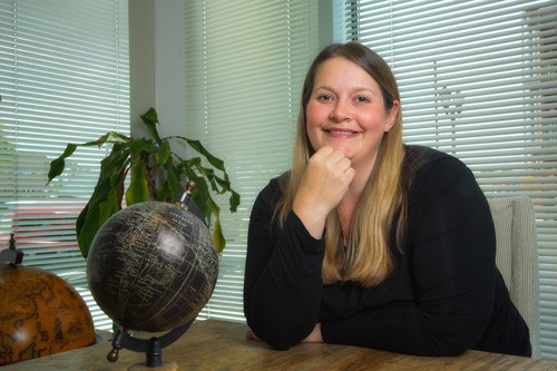 Photo of Helen Jugovic Tarokic (JD '06) sitting at a table in her office.