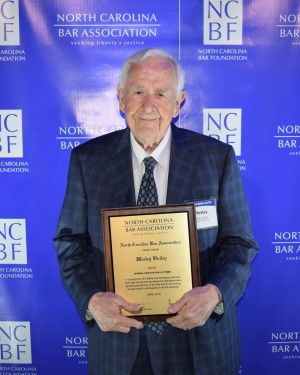 Photo of Wesley Bailey (BA' 54, LLB '55) holding plaque