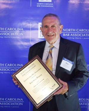 Photo of J. Gary Vannoy (BA '62, LLB '64) holding plaque.
