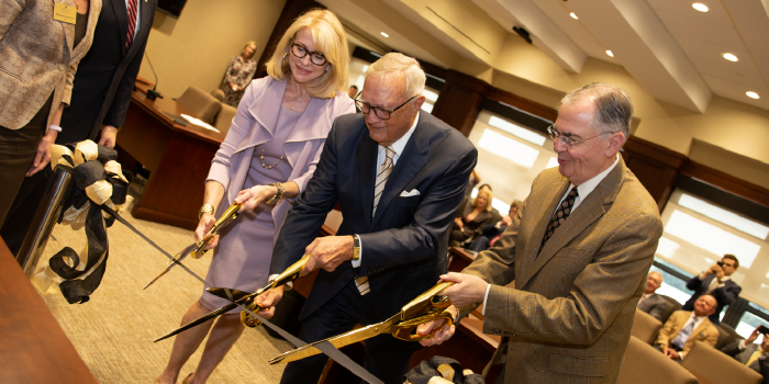 Photo of group of people cutting a ribbon at dedication ceremony