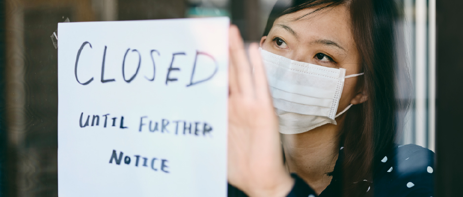 woman with sign that says closed until further notice
