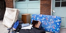 Mattresses and household goods piled against garage door, illustrating eviction
